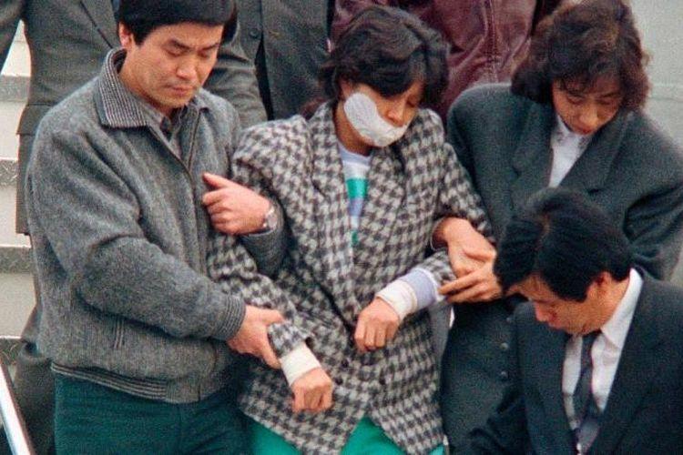 Kim Hyon Hui digiring para agen Korea Selatan saat tiba di Seoul pada 15 Desember 1987 setelah diekstradisi dari Bahrain.