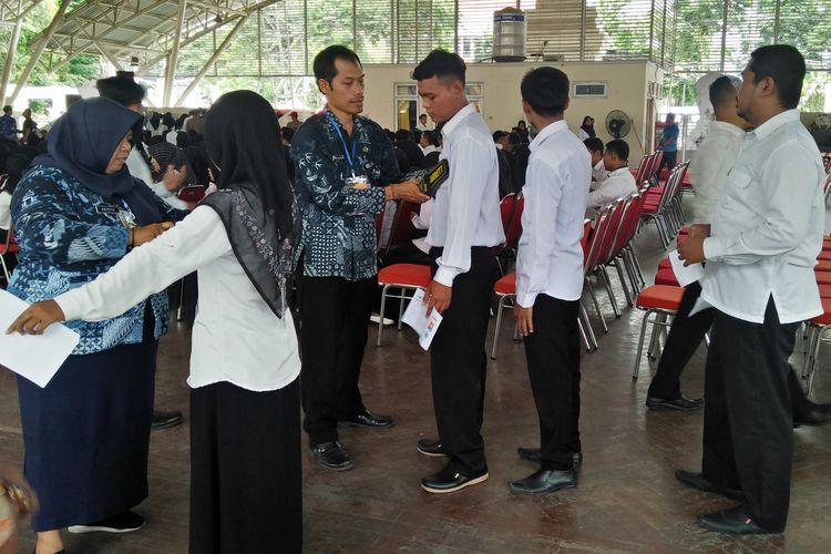 Panitia saat memeriksa calon peserta, sebelum mereka memasuki gedung guna mengikuti tes SKD CPNS Kabupaten Gresik.