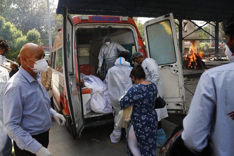Petugas kesehatan bersiap untuk mengambil dari jenazah ambulans enam orang yang meninggal karena Covid-19 untuk dikremasi, di New Delhi, India, Senin (19/4/2021).