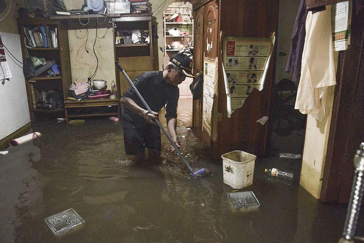 Warga beraktivitas di rumahnya saat banjir di kampung Buaran Jaya, Harapan Mulya yang terendam banjir di Bekasi, Jawa Barat, Selasa (21/1/2020). Menurut warga banjir memasuki rumah warga pada pukul 04.00 WIB setinggi 60-90 cm akibat curah hujan tinggi dan saluran drainase yang buruk.