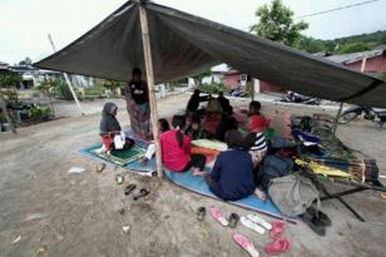 Korban gempa mendapat perawatan di Posko Puskesmas, Lampahan, Kecamatan Timang Gajah, Kabupaten Bener Meriah, Aceh Selasa (2/7/2013). Gempa berkekuatan 6.2 SR di Aceh, menghancurkan rumah dan mengakibatkan tanah longsor. Tujuh orang tewas dan puluhan terluka.