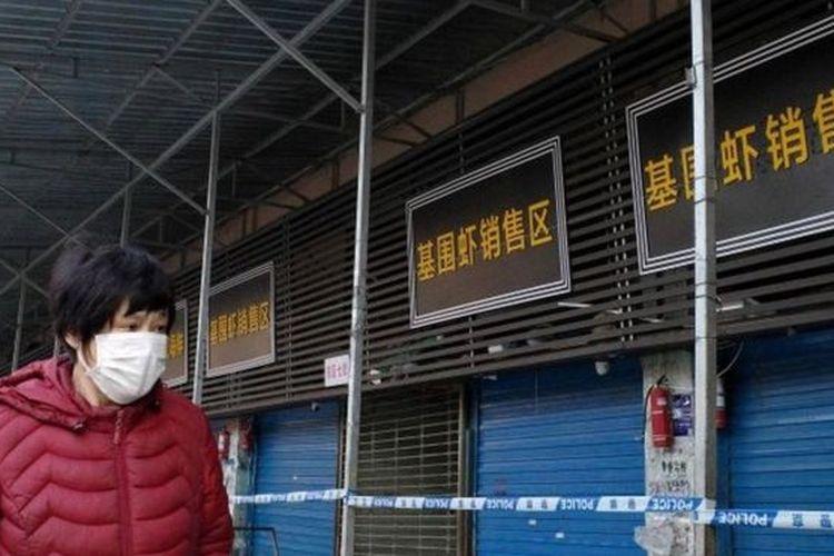 Seorang perempuan mengenakan masker melintas di kawasan pertokoan China. Sejak Desember 2019, China dilanda virus misterius mirip SARS. yang sudah menelan dua korban jiwa.