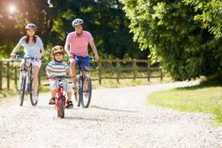 Anak bermain sepeda bersama orangtua
