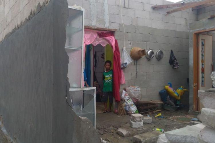 Seorang anak tengah menengok bagian belakang rumah yang rusak akibat terjangan puting beliung di Desa Sungai Buntu, Kecamatan Pedes, Kabupaten Karawang, Kamis (9/1/2020).