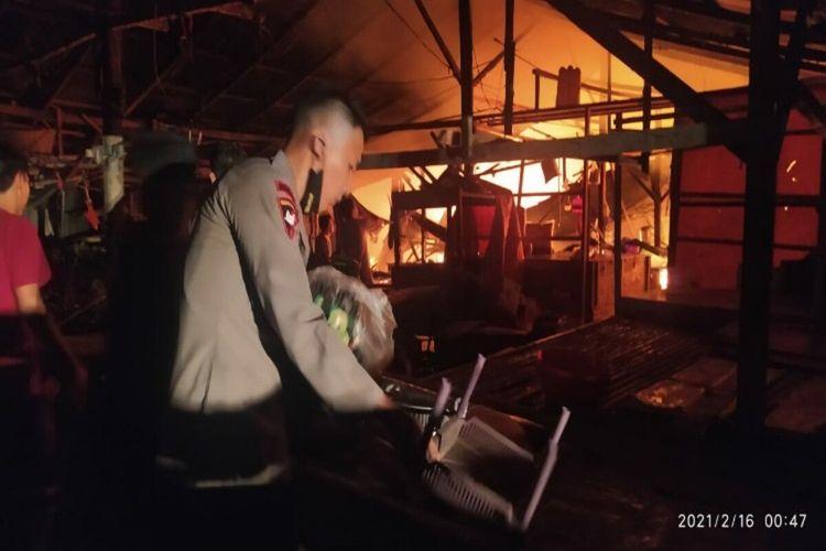 Pasar Perum Paniki di Kota Manado, Sulawesi Utara, terbakar pada Selasa (16/2/2021) dini hari. Sebanyak 140 kios ludes terbakar. Polisi membantu memadamkan api.