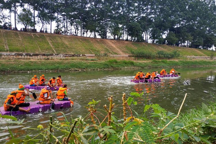 Pasukan oranye UPK Badan Air Duren Sawit lomba balap dayung di aliran Banjir Kanal Timur, Jakarta Timur, Sabtu (17/8/2019).