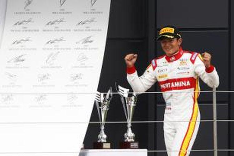 Pebalap Campos Racing asal Indonesia, Rio Haryanto, merayakan kemenangan di atas podium Sirkuit Silverstone setelah memenangi sprint race GP2 Inggris, Minggu (5/7/2015).