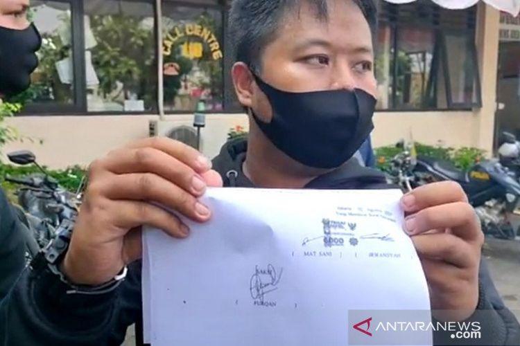 Petugas Dinas Perhubungan berinisial IR memperlihatkan selembar kertas yang disebut sebagai surat perdamaian dengan seorang pengendara angkot di halaman parkir Mapolsek Pulo Gadung, Jakarta Timur, Minggu (2/7/2020). Perikaian anggota Dishub dan pengendara angkot dipicu senggolan sehingga berujung pemecahan kaca kendaraan.