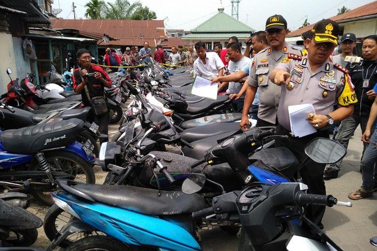 Kapolres Pelabuhan Belawan AKBP Ikhwan Lubis berdiri di antara puluhan sepeda motor yang diduga hasil kejahatan di Polsek Medan Labuhan.
