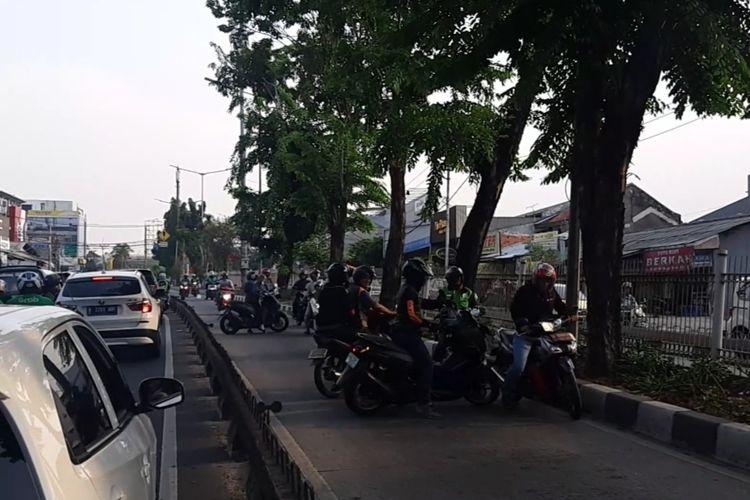 Pengendara motor yang masuk jalur bus Transjakarta berusaha memutar balik sebab mengetahui ada aparat kepolisian yang telah berjaga di ujung jalur untuk menilang para pengendara