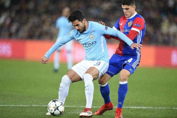 Gelandang Manchester City, Ilkay Guendogan, mencoba melindungi bola dari upaya pemain FC Basel merebutnya pada pertandingan babak 16 besar Liga Champions, 13 Februari 2018.