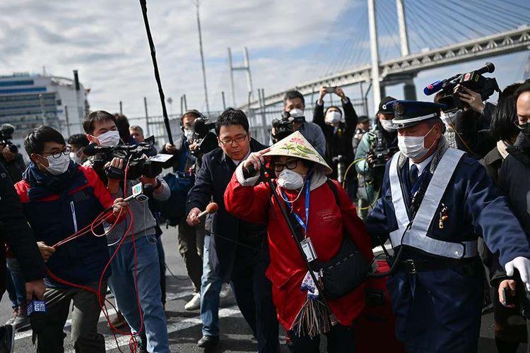 Para penumpang kapal pesiar Diamond Princess yang dinyatakan tidak negatif virus corona keluar setelah menjalani karantina, di Terminal Daikoku Pier Cruise di Yokohama, Jepang, Rabu (19/2/2020). Setidaknya 500 penumpang diizinkan keluar setelah dikarantina selama 14 hari, menyusul kabar terdapat 542 penularan positif corona di dalam kapal tersebut.