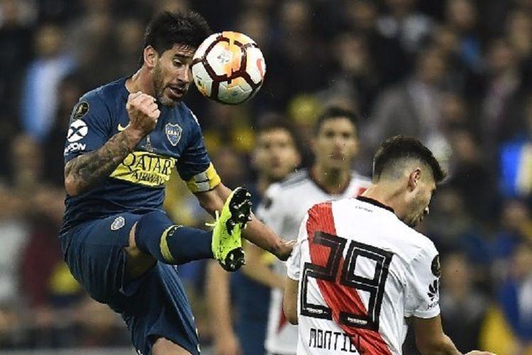 Gonzalo Montiel kalah dalam duel udara dengan Pablo Perez pada laga final Copa Libertadores antara Boca Juniors vs River Plate di Stadion Santiago Bernabeu, 9 Desember 2018.