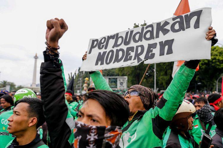 Pengemudi ojek online melakukan aksi unjuk rasa di depan Istana Negara, Jakarta Pusat, Selasa (27/3/2018). Massa dari pengemudi ojek online menuntut pemerintah membantu untuk berdiskusi dengan perusahaan transportasi online agar merasionalkan tarif.