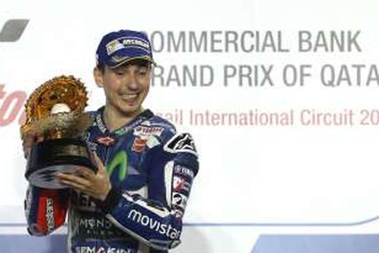 Pebalap Movistar Yamaha asal Spanyol, Jorge Lorenzo, merayakan kemenangan di atas podium Sirkuit Losail setelah memenangi balapan GP Qatar, Minggu (20/3/2016).