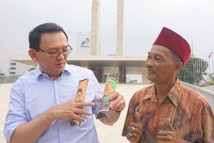 Mantan Gubernur DKI Jakarta Basuki Tjahaja Purnama dihampiri pedagang kerak telor ketika berkunjung ke Taman Lapangan Banteng, Jakarta, Jumat (9/7/2019). Peristiwa itu kemudian ditayangkan dalam vlog Ahok di Youtube.