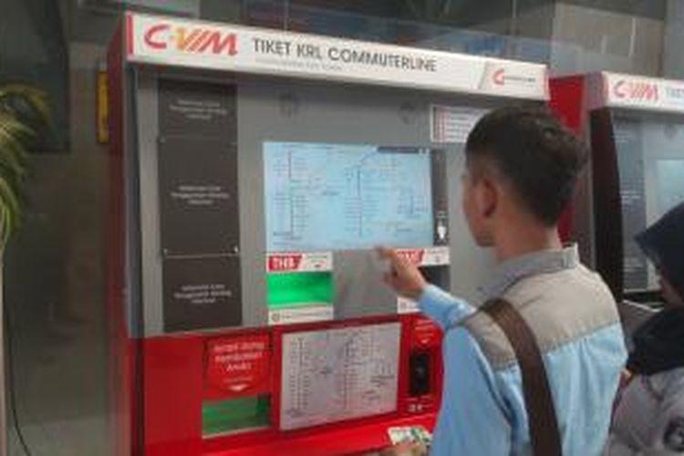 Salah seorang calon penumpang menjajal mesin tiket kereta rel listrik (KRL) commuter line yang terpasang di Stasiun Sudirman, Sabtu (9/1/2016). Tampak di sebelahnya ada salah seorang petugas yang membantu mendampingi penumpang yang hendak melakukan transaksi.