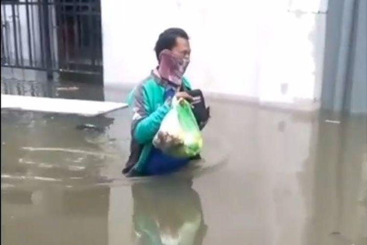 Ali Romadhon antar pesnanan dengan berjalan jaki terjang banjir di Semarang