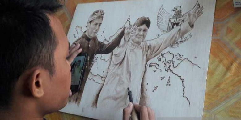 Pelukis muda Temanggung mengabadikan calon presiden Joko Widodo dan Prabowo Subianto bergandeng tangan saat deklarasi kampanye damai Pemilu 2019 dalam lukisan pyrography.