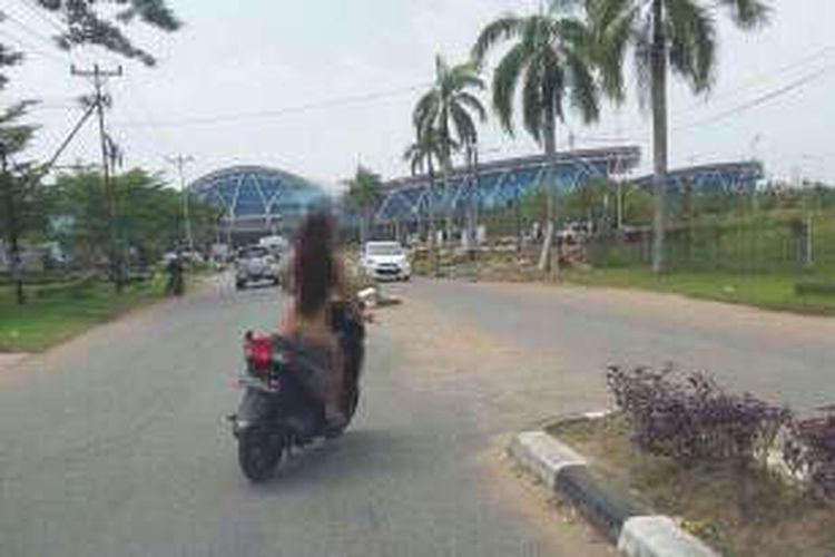 Aksi seorang perempuan yang nekat mengendarai sepeda motor tanpa busana memasuki wilayah Bandara Supadio Pontianak yang di unggah warga di media sosial, Minggu (15/1/2017)