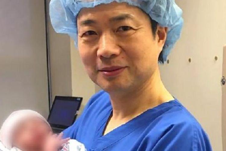 John Zhang menggendong bayi dari tiga orang tua kandung hasil langkah kontroversial yang ditempuhnya.