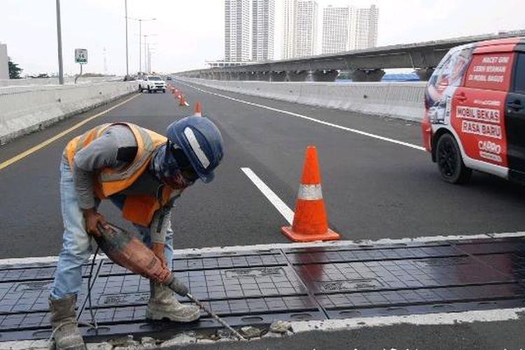 Salah satu tenaga kerja sedang memasang siar muai atau expansion joint di Jalan Tol Layang Mohammed Bin Zayed, Jakarta, Minggu (22/8/2021).