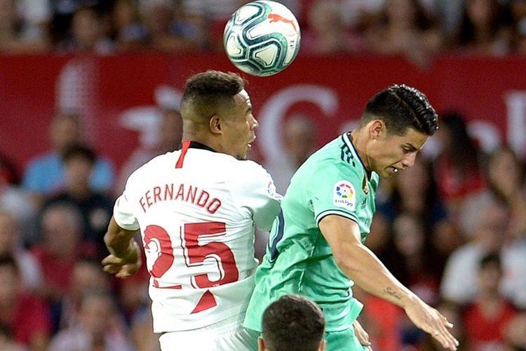 Fernando dan James Rodriguez berebutan bola di udara pada pertandingan Sevilla vs Real Madrid dalam lanjutan La Liga Spanyol di Stadion Ramon Sanchez Pizjuan, 22 September 2019.