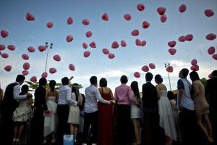 Sebanyak 138 pasangan muda di Malaysia menikah massal di sebuah kuil Konghucu di Kuala Lumpur, bertepatan dengan hari kasih sayang, Jumat (14/2/2014). Usai mengikat janji pernikahan, mereka melepaskan balon berbentuk hati berwarna merah ke angkasa.