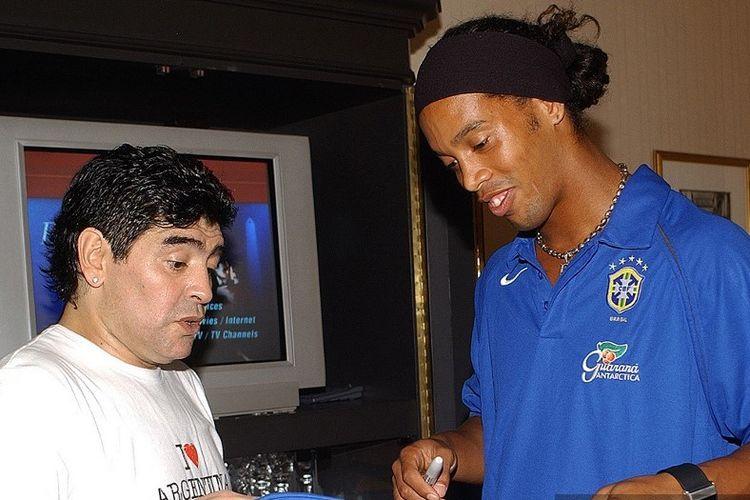 Mantan pemain sepak bola Argentina Diego Maradona (kiri) dan Ronaldinho dari Brasil melihat tanda tangan Maradona di sebuah kaos Argentina di sebuah hotel di Buenos Aires akhir 06 Juni 2005. Tim sepak bola nasional Brasil akan menghadapi Argentina dalam pertandingan kualifikasi Piala Dunia FIFA Jerman 2006, selanjutnya 08 Juni