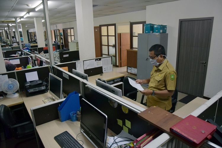 Seorang pegawai negeri sipil (PNS) Pemprov Riau mengenakan masker saat mendapat giliran masuk bekerja di Dinas Komunikasi Informatika dan Statistik Riau, di Kota Pekanbaru, Senin (20/4/2020). Menteri Pendayagunaan Aparatur Negara dan Reformasi Birokrasi memperpanjang kebijakan bekerja dari rumah bagi PNS hingga 13 Mei 2020 karena wabah COVID-19, dan PNS disesuaikan dengan sistem kerja dengan adanya Pembatasan Sosial Berskala Besar (PSBB). ANTARA FOTO/FB Anggoro/hp.