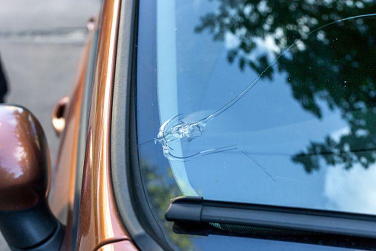 Ilustrasi mobil rusak karena lemparan batu.