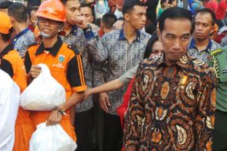 Presiden Joko Widodo membagikan paket sembako di Lapangan Bedeng, Pisangan Baru Tengah, Pisangan Baru, Kecamatan Matraman, Kota Jakarta Timur, Selasa (8/9/2015).