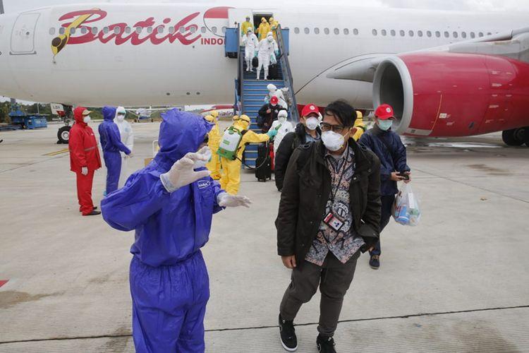 Petugas medis mengarahkan warga negara Indonesia (WNI) dari Wuhan, China yang telah disemprot cairan disinfektan setibanya di Bandara Hang Nadim, Batam, Kepulauan Riau, Minggu (2/2/2020). Sebanyak 238 WNI dari Wuhan tersebut selanjutnya dipindahkan ke Natuna untuk menjalani observasi selama kurang lebih dua minggu guna memastikan kesehatannya dan terbebas dari virus corona.