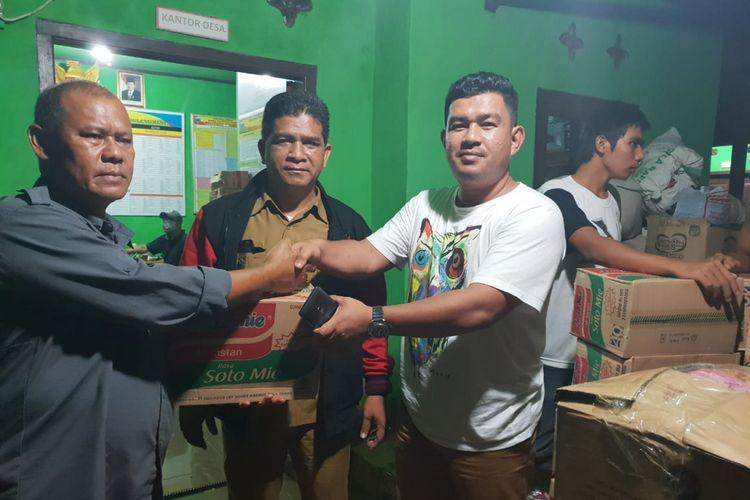 Kepala Badan Penghubung Pemerintah Aceh (BPPA), Almuniza Kamal (kanan) menyerahkan bantuan masa darurat bencana pacsa-tsunami kepda Lurah Desa     Desa Tingkilsari, Kecamatan Cimanggu, Pandeglang, Provinsi Banten, Senin (24/12/2018).