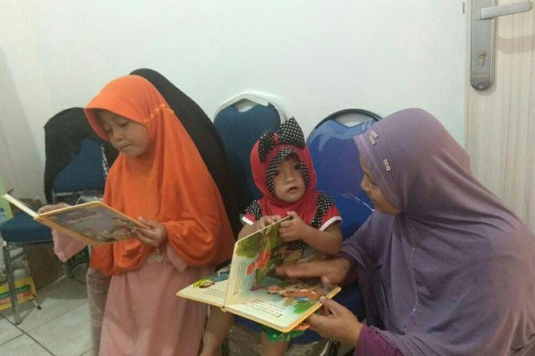 Orangtua dan anaknya yang terpapar asap membaca buku di posko evakuasi korban bencana asap karhutla di Pekanbaru, Riau, Kamis (19/9/2019).