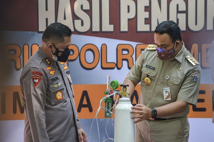 Gubernur DKI Jakarta Anies Baswedan (kanan) berbincang dengan Kapolda Metro Jaya Irjen Pol Mohammad Fadil Imran (kiri) saat penyerahan barang bukti tabung oksigen hasil pengungkapan kasus tindak kejahatan di Jakarta, Selasa (27/7/2021). Sebanyak 138 tabung yang sudah dilakukan pemeriksaan oleh Kementerian Kesehatan tersebut diserahkan kepada Pemerintah Provinsi DKI Jakarta untuk digunakan sebagai penanggulangan Covid-19 di sejumlah fasilitas pelayanan kesehatan di Jakarta.