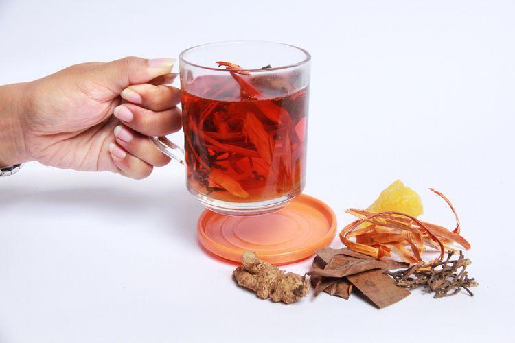 Ilustrasi segelas wedang uwuh panas, minuman herbal terbuat dari berbagai dedaunan kering.