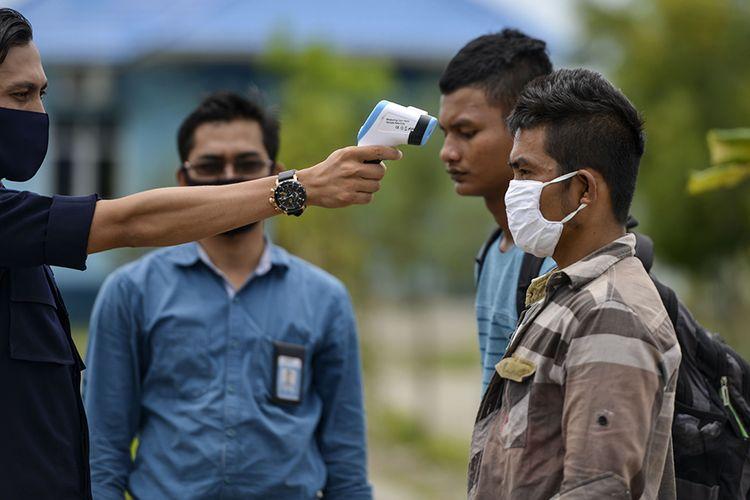Petugas mengecek suhu tubuh nelayan Myanmar saat persiapan untuk dideportasi di Pangkalan Pengawasan Sumber Daya Kelautan dan Perikanan (PSDKP) Lampulo, Banda Aceh, Rabu (5/8/2020). Dari 15 nelayan asal Myanmar yang ditangkap bersama 3 unit kapal berbendera Malaysia pada 2019 dan 2020 terkait kasus illegal fishing di ZEE Selat Melaka wilayah perairan Indonesia, 9 ABK di antaranya dideportasi ke negara asal, sedangkan 6 lainnya yang terdiri dari nakhoda dan ABK ditahan untuk proses penyidikan dan saksi.
