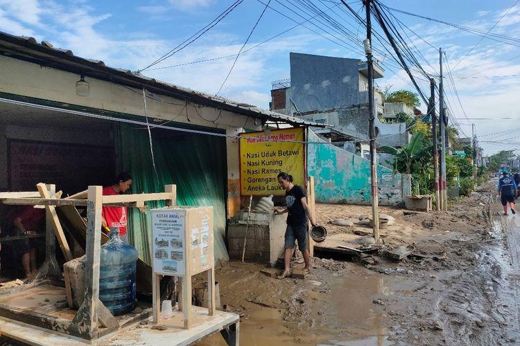 Sejumlah warga di Pondok Gede Permai, Bekasi membersihkan lumpur dan sampah akibat banjir, Minggu (21/2/2021)