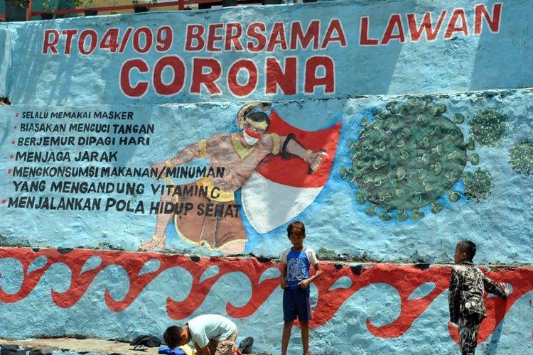 Anak-anak bermain di dekat mural tentang corona di Babakan Pasar, Kota Bogor, Jawa Barat, Kamis (17/09)