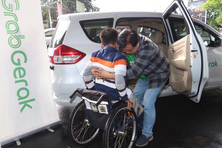 Mitra pengemudi GrabGerak membantu pelanggan dengan disabilitas.