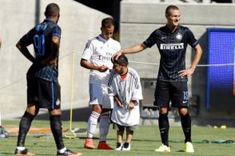 Pemain Real Madrid, Lucas Vazquez, membubuhkan tanda tangan untuk seorang anak yang berada di depan pemain Inter Milan, Nemanja Vidic, dalam laga International Champions Cup 2014 di California Memorial Stadium pada 26 Juli 2014 di Berkeley, California.