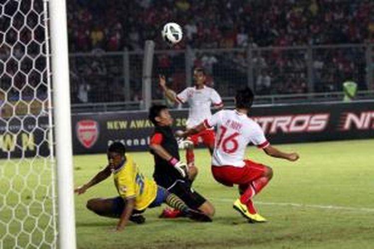 Kiper tim Indonesia Dream Team, Kurnia Meiga (tengah) meninju bola dari pemain Arsenal saat pertandingan persahabatan di Stadion Utama Gelora Bung Karno, Jakarta Pusat, Minggu (14/7/2013).