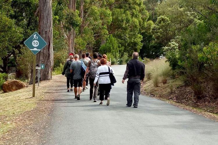 Para wisatawan berjalan kaki menuju dermaga tempat perahu Tasman Cruise ditambatkan.