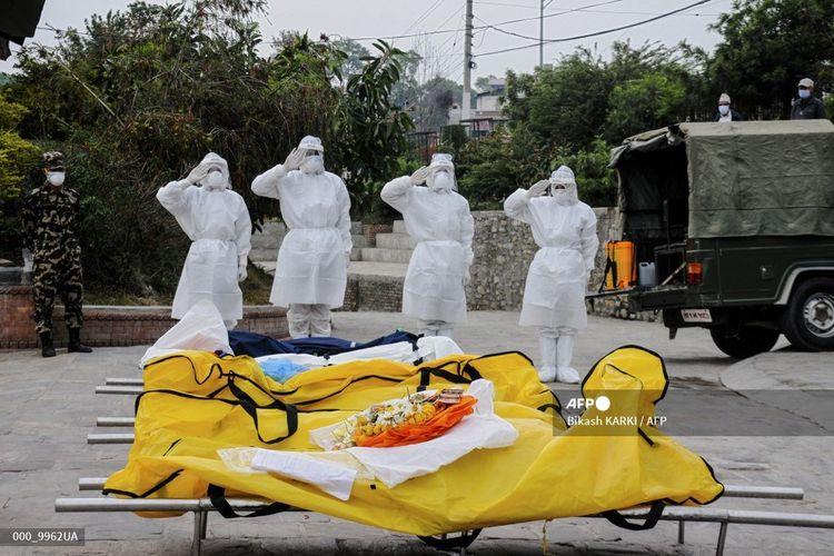 Empat tentara Nepal, mengenakan pakaian pelindung medis, memberikan penghormatan kepada jenazah Covid-19 di luar krematorium Kathmandu, pada 1 Mei 2021.