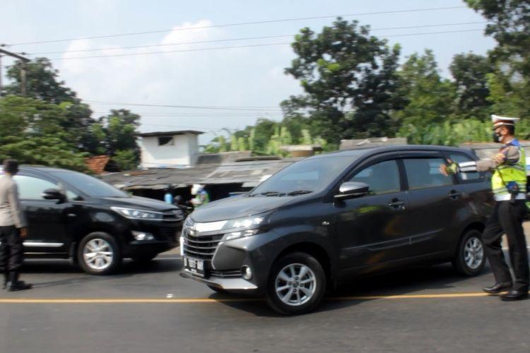 Petugas memutar balik kendaraan yang hendak menuju Cianjur di kawasan Jembatan Citarum yang merupakan wilayah perbatasan antara Cianjur dan Bandung Barat, Kamis (6/5/2021). Para pengendara yang tidak membawa surat keterangan bebas Covid-19 langsung diputar balik.