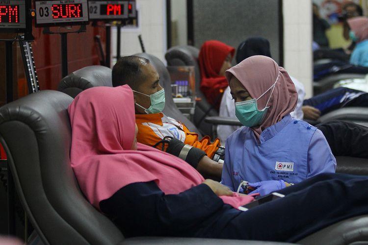 Petugas melayani pendonor di ruang donor darah Unit Transfusi Darah (UTD) Palang Merah Indonesia (PMI) Kota Surabaya, Jawa Timur, Kamis (19/3/2020). PMI Kota Surabaya kekurangan pasokan darah sekitar 60 persen dari rata-rata sehari sebanyak 450 pendonor (450 kantong darah) menjadi sekitar 140 pendonor karena adanya himbauan pembatasan kegiatan sosial guna mencegah penyebaran COVID-19.