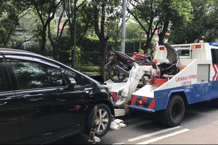 Mobil derek membawa mobil dan motor yang terlibat kecelakaan di Jalan Dharmawangsa Raya tepatnya di dekat Sanatorium Dharmawangsa, Pulo, Kebayoran Baru, Jakarta Selatan pada Senin (30/8/2021) siang.
