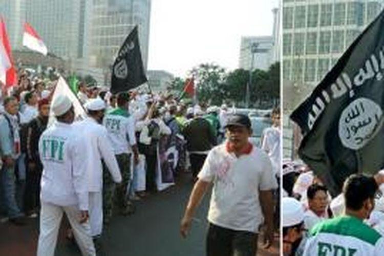 Bendera hitam dengan lambang ISIS dibawa salah satu peserta aksi di Bundaran HI, Jakarta, Jmat (11/7/2014). Foto diambil dari Twitter.