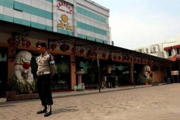 Polisi berjaga di Vihara Ekayana Buddhist Centre, Jakarta Barat, Senin (5/8/2013), pascaledakan bom pada Minggu malam. Terjadi ledakan bom berdaya ledak kecil di dalam vihara yang melukai tiga orang. Sebuah paket bom ditemukan gagal meledak.
